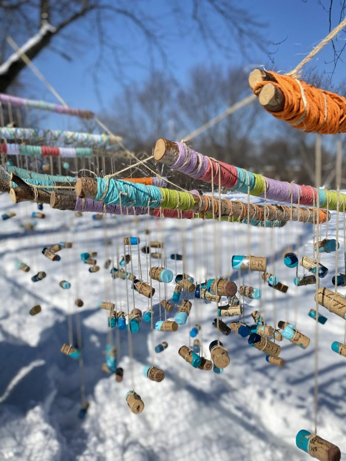 Sticks wrapped in colorful yarn are tied together with blue-dipped corks hanging beneath them on strings. There is snow in the background.
