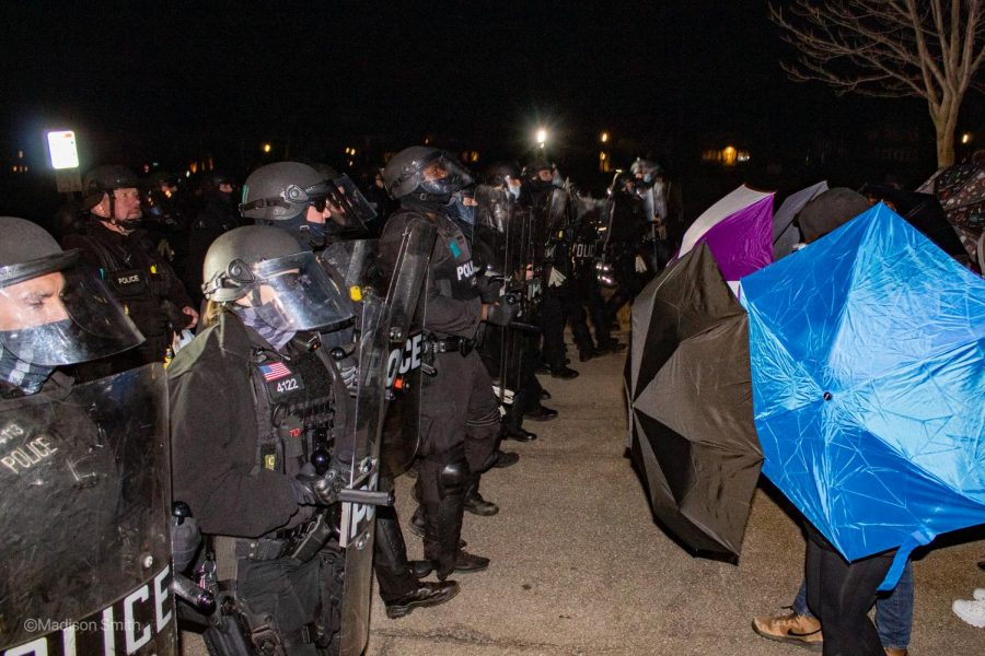 A+line+of+police%2C+fully+armed+in+riot+gear%2C+faces+off+with+protesters+who+are+protecting+their+faces+with+umbrellas.