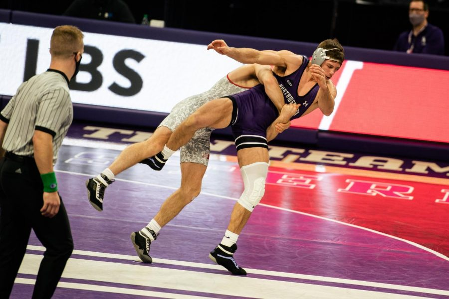 Ryan Deakin in a wrestling match against Wiconsin's Garrett Model. Deakin is undefeated on the season, and is coming off a dominating performance against Minnesota's Brayton Lee on his way to the Big Ten Tournament.