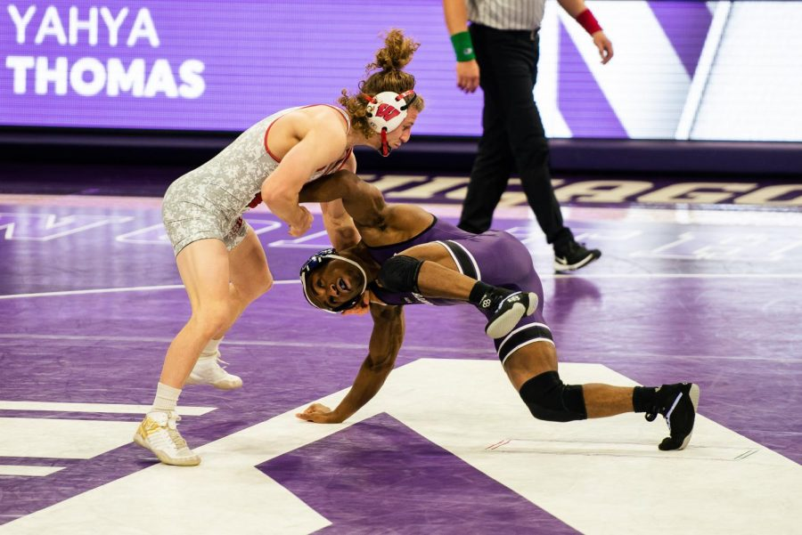Northwestern wrestler tries to tackle opponent from the bottom, reaching with arms up at opponent's core.