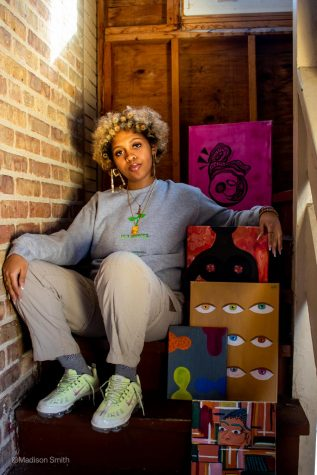 """Ziana sits in a stairwell with several of her paintings. She wears a gray sweatshirt with the phrase """"still growing"""" in green."""