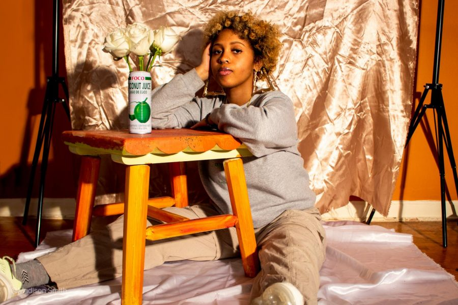 Ziana sits down in front of a light gold backdrop, leaning on a small table with a white and green can holding white roses. Ziana wears a gray sweatshirt and khaki pants.