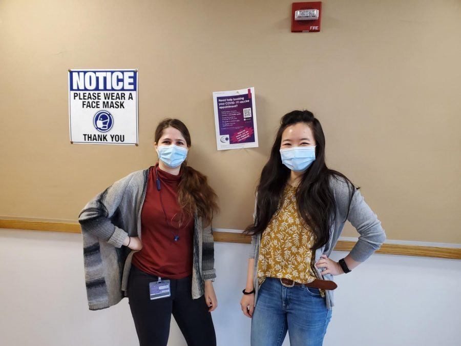 Two women in gray cardigans and jeans stand in front of a beige and white wall. Between them, a paper flyer reads: Need help booking your COVID-19 vaccine appointment?