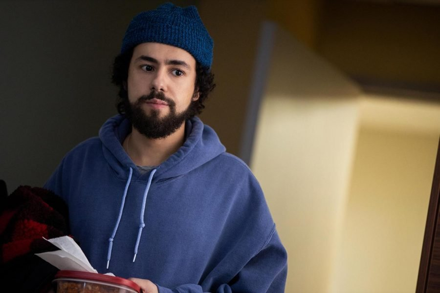 A+picture+of+Ramy+Youssef%2C+who+is+wearing+a+dark+blue+hoodie+and+navy+beanie+while+holding+pieces+of+paper+and+red+cloth.+In+the+background+is+an+open+door+with+yellow+light+streaming+in.