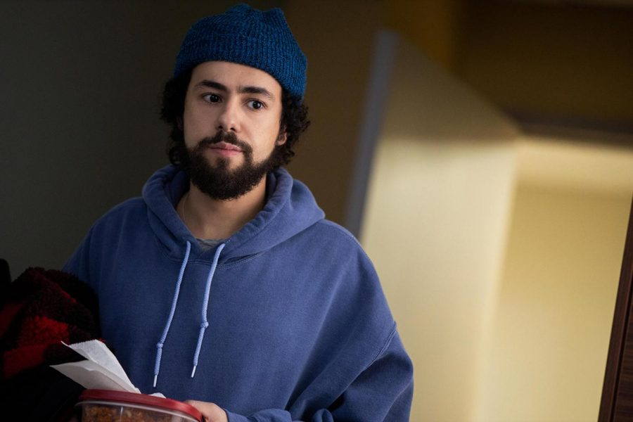 A picture of Ramy Youssef, who is wearing a dark blue hoodie and navy beanie while holding pieces of paper and red cloth. In the background is an open door with yellow light streaming in.