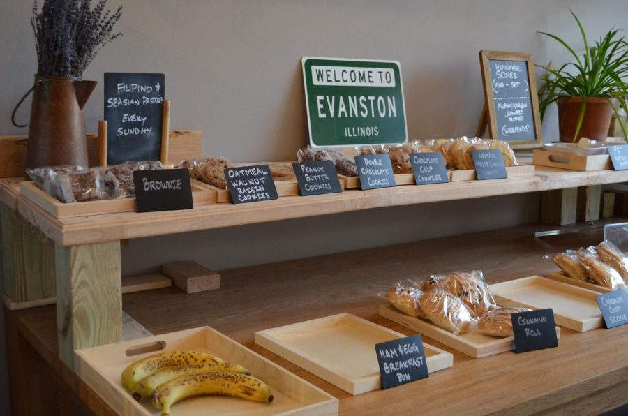 "Two shelves of pastries, cookies and bananas. Each item has a black label with the name of the item written in chalk, and above the display is a green sign saying ""Welcome to Evanston, Illinois."""