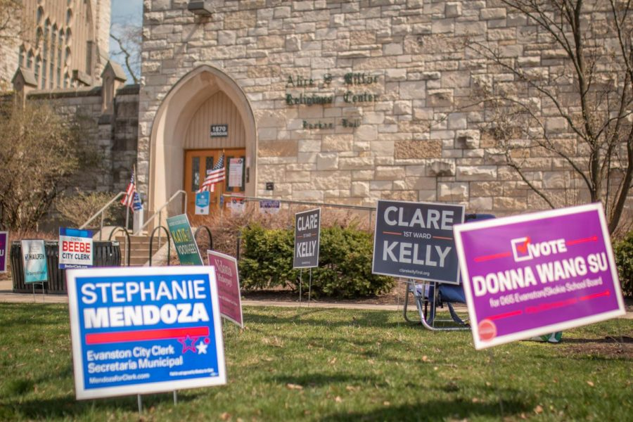 Brightly colored campaign signs dot the lawn of a tan brick building.