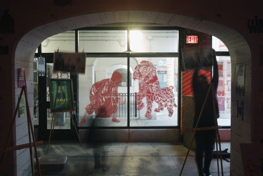 A+window+display+that+shows+a+red+animal+on+the+right+panel+and+a+red+person+on+the+left%2C+both+facing+toward+each+other.+Around+the+window+are+displays+of+different-colored+paintings.