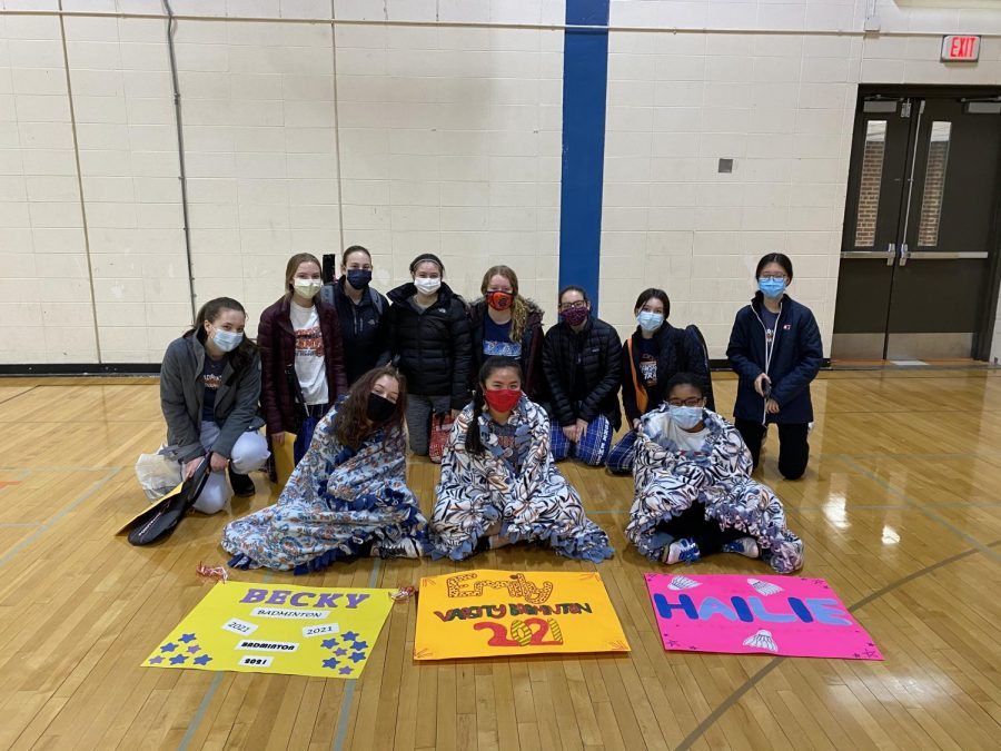 Eleven girls wearing masks sit on the wooden floor of a high school gym. There are three posters on the floor in front of them: one is yellow, one is orange, and one is yellow.
