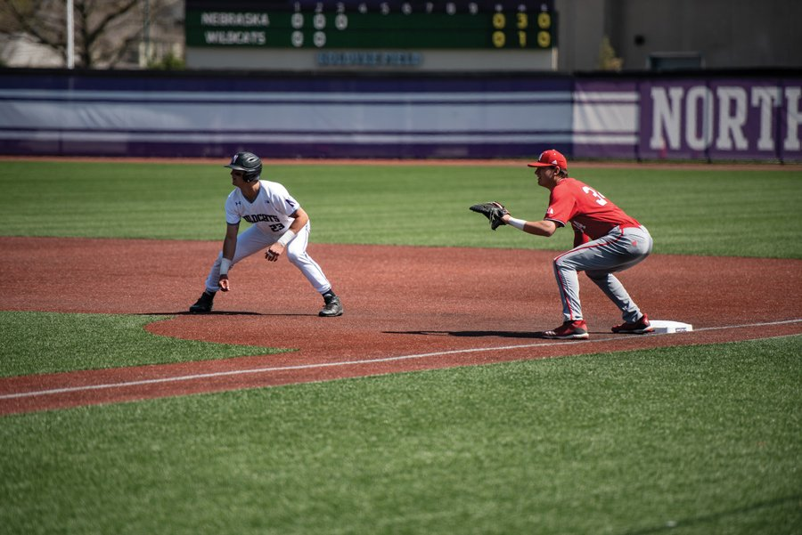 Northwestern player crouches on the basepath, leading off from first base.