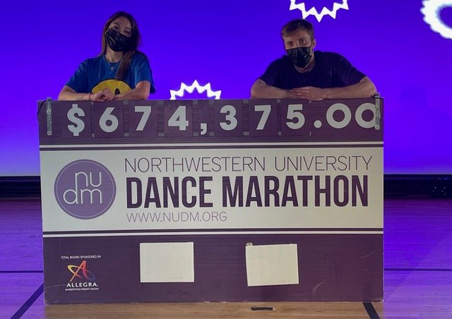 Two students hold a purple check that says $674,375.00, raised by NUDM.