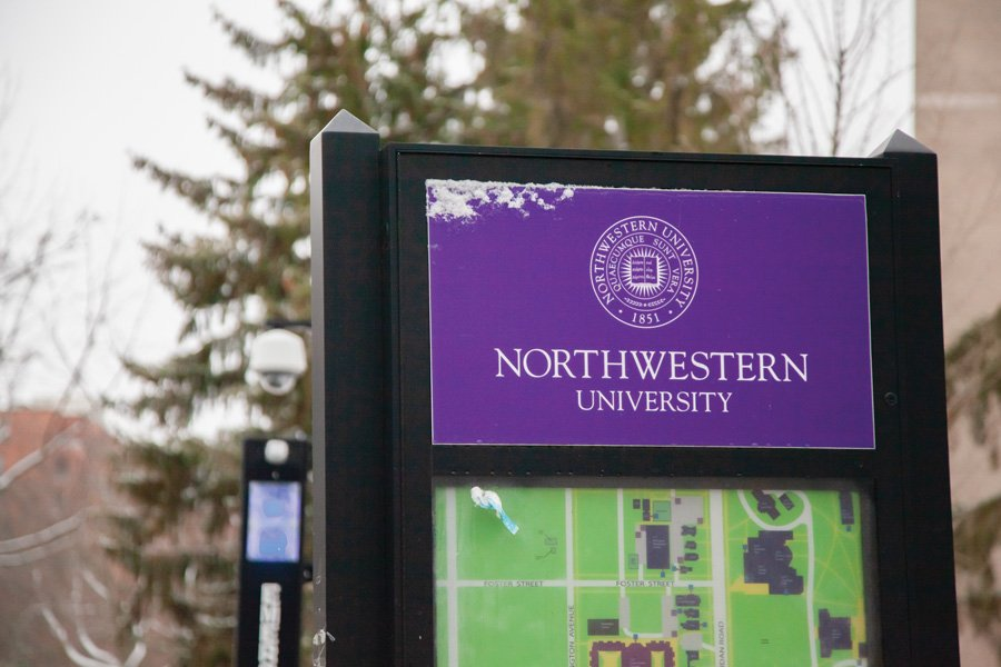 """A black metal marker displays a purple sign with words """"Northwestern University."""" Below the sign is a green map of the campus. Behind the marker are dark green leaves and a lamppost."""