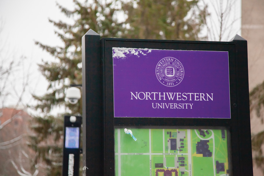 "A black metal marker displays a purple sign with words ""Northwestern University."" Below the sign is a green map of the campus. Behind the marker are dark green leaves and a lamppost."