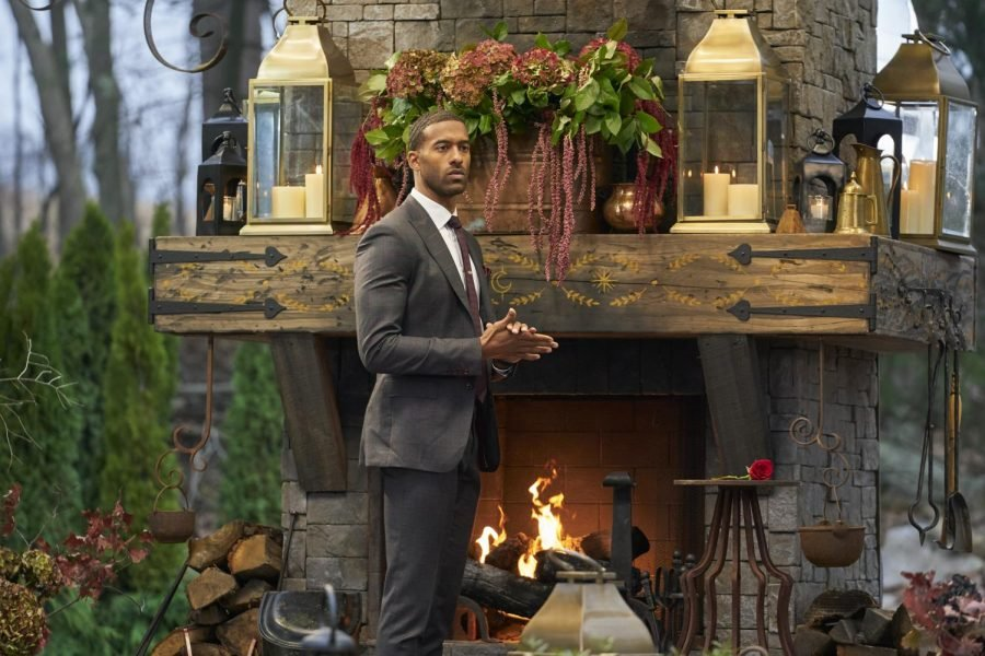 A man in a suit stands in front of a wood fireplace.