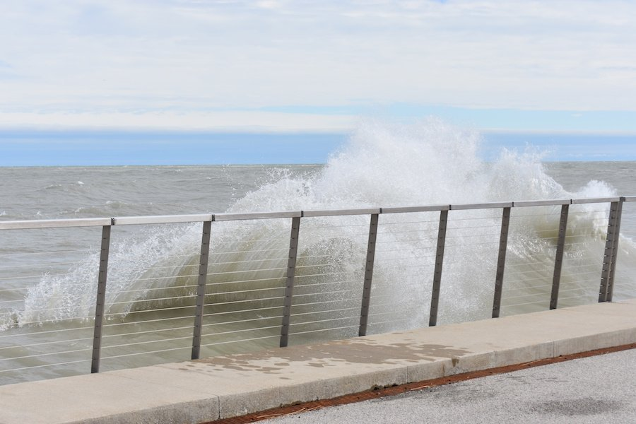 The waves of Lake Michigan crash against a row of silver fencing with gaps in between the horizontal bars set against a blue, cloudy sky. There is water on the concrete sidewalk and a bit of the gray road is visible in the corner of the image.