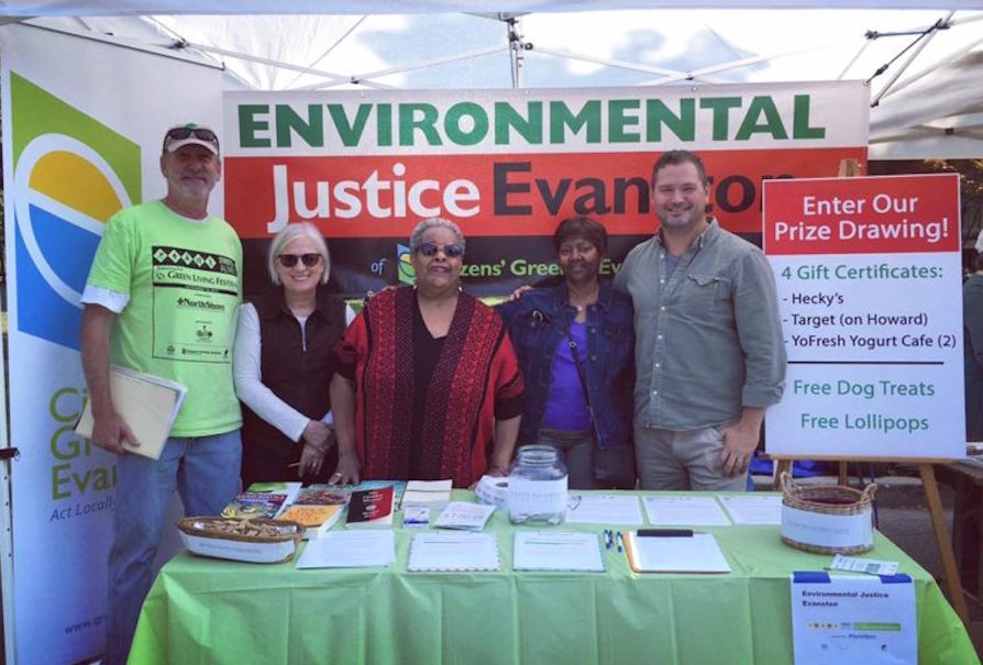 "Five people standing in front of a table with an ""Environmental Justice Evanston"" banner in the background."
