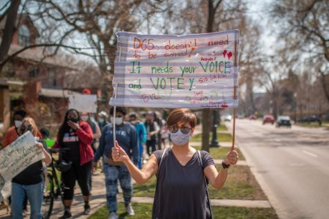 """Martin, wearing a blue shirt and a striped mask, holds up a sign stating """"D65 doesn't need to be saved! It is in good hands. It needs your voice and vote!"""" The sign also has the names of D65 board members Soo La Kim, Elisabeth """"Biz"""" Lindsay-Ryan, Joey Hailpern, and newcomer Marquise Weatherspoon. Martin stands off to the side while event participants march past on the sidewalk carrying signs."""