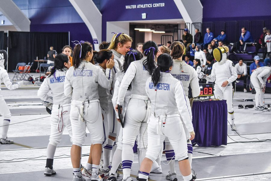 Approximately a dozen members of Northwestern's women's fencing team huddle together to celebrate a win, all wearing their fencing uniforms.