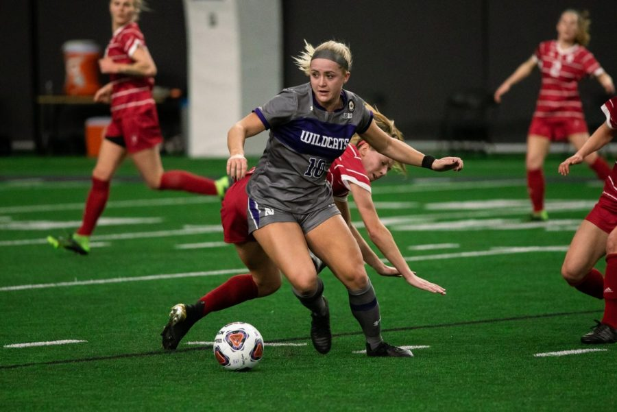 Women's soccer player Olivia Stone dribbles the soccer ball on a soccer field, surrounded by opposing team players in red.