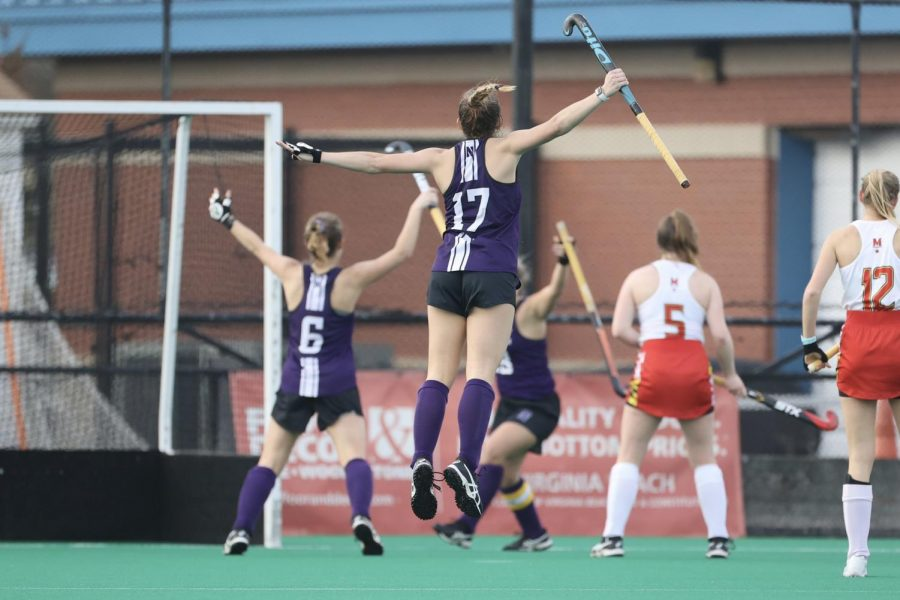 Girl with long ponytail in purple and white uniform jumps with a field hockey stick in hand and back facing the camera.