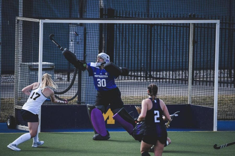 Northwestern field hockey goalie Annabel Skubisz holds her stick up in the air to deflect a ball coming toward the goal.