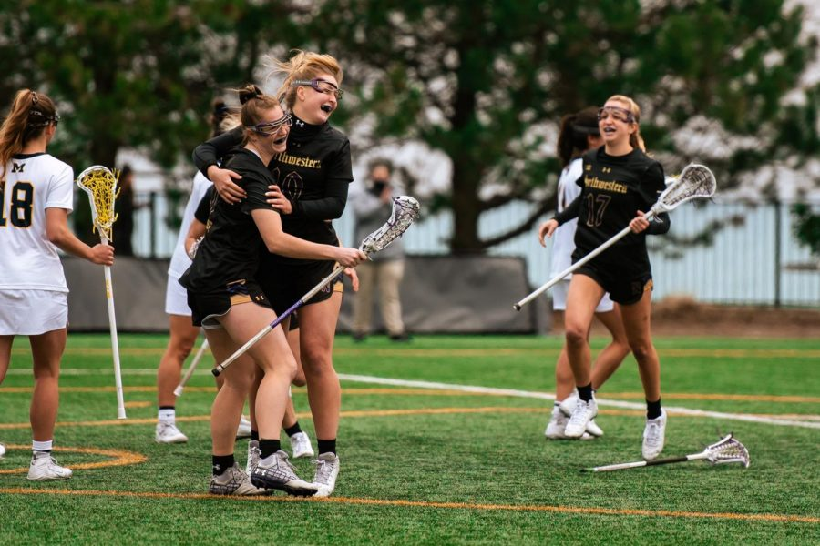 Izzy Scane (left) and Dylan Amonte hug while celebrating a goal, with Taylor Pinzone running toward them.