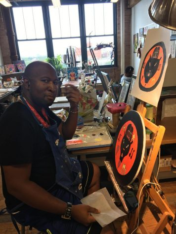 David Holt works on a piece in an art studio. His art piece is a circular portrait in an orange background