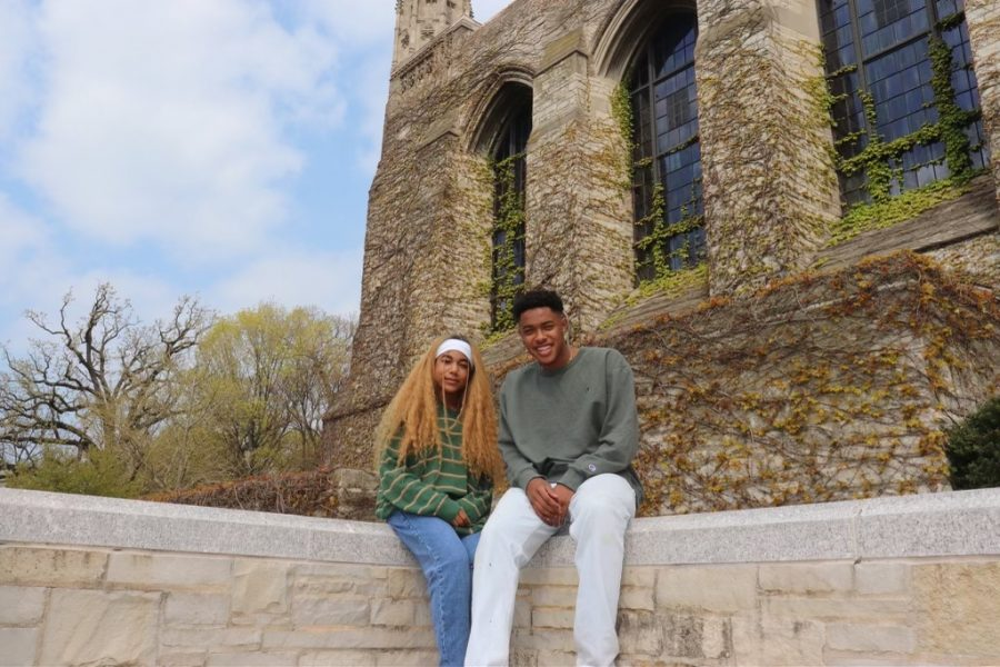 Christian Wade and Ada Ogbonna sit side by side on a concrete ledge in front of Deering Library. Ogbonna is wearing a long sleeve, striped green sweater with blue jeans and Wade is wearing white jeans with an olive green long sleeve shirt. There are trees behind them and a blue, cloudy sky and vines all across the library background.