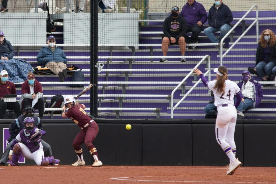Northwestern player in white uniform with arm raised prepares to pitch.