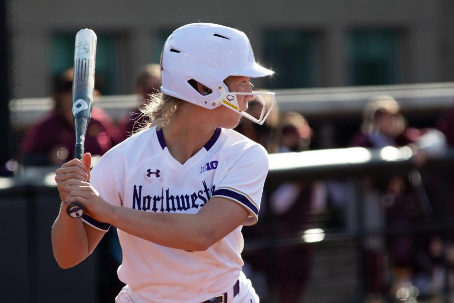 player in white uniform stares forward with black bat behind her head and white helmet