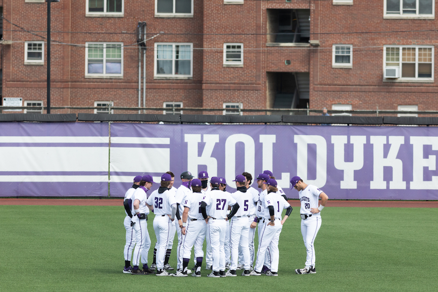 Baseball players in purple and white uniforms stand in a huddle on the outfield grass.