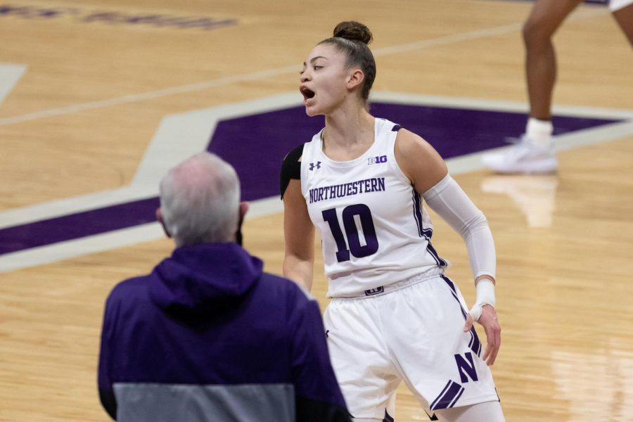 Northwestern+athlete+wearing+purple-and-white+jersey+celebrates+while+side-stepping+down+court