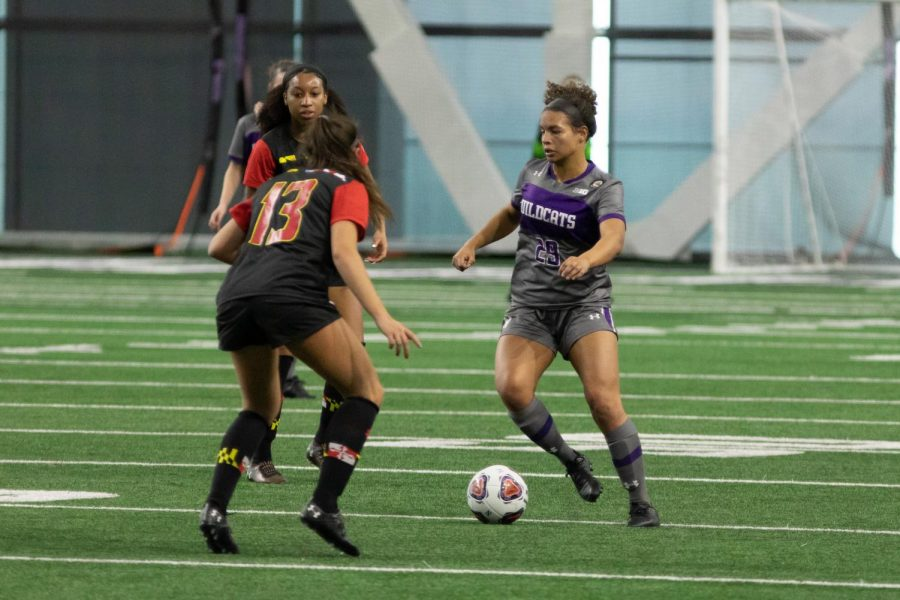 Women's soccer player wearing gray and purple uniform kicks the ball around women's soccer players in black, red and yellow uniforms