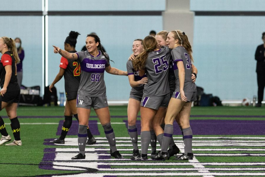 Women's soccer players wearing gray and purple uniforms hug each other.