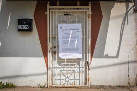 A cream-colored building with a white door. A white rectangular poster with black lettering is taped onto the door.