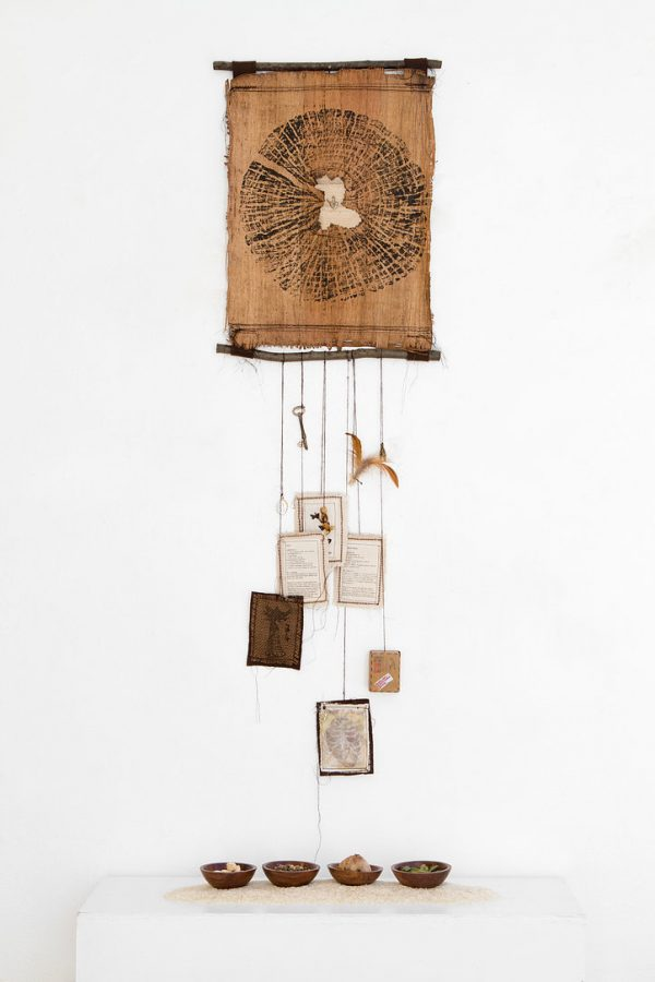 A brown scroll of papyrus with branches on the top and bottom. The ink on the papyrus creates a circle design. Below, there are various hanging objects.
