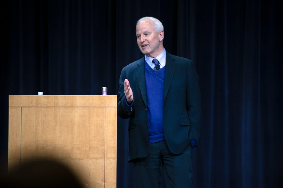 University President Morton Schapiro gestures while standing in front of a light wooden podium and navy curtains. He wears a suit, tie, and purple vest.