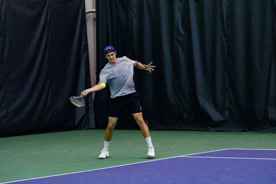 Northwestern+men%E2%80%99s+tennis+player+wearing+gray+shirt+and+black+shorts+returns+a+shot.
