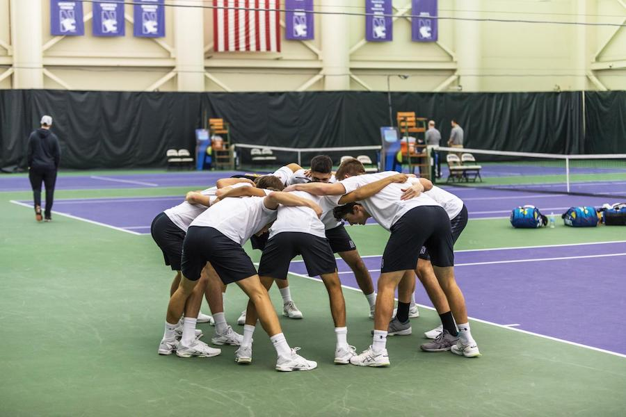 Northwestern men's tennis players wearing white shirts and black shorts huddle on the court
