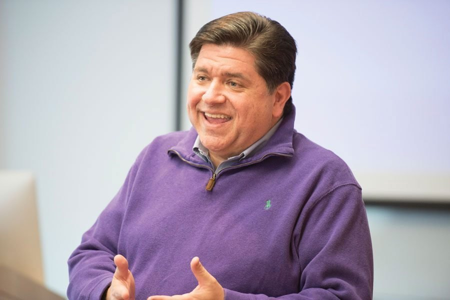 Governor J.B. Pritzker smiles and gestures with his hands.