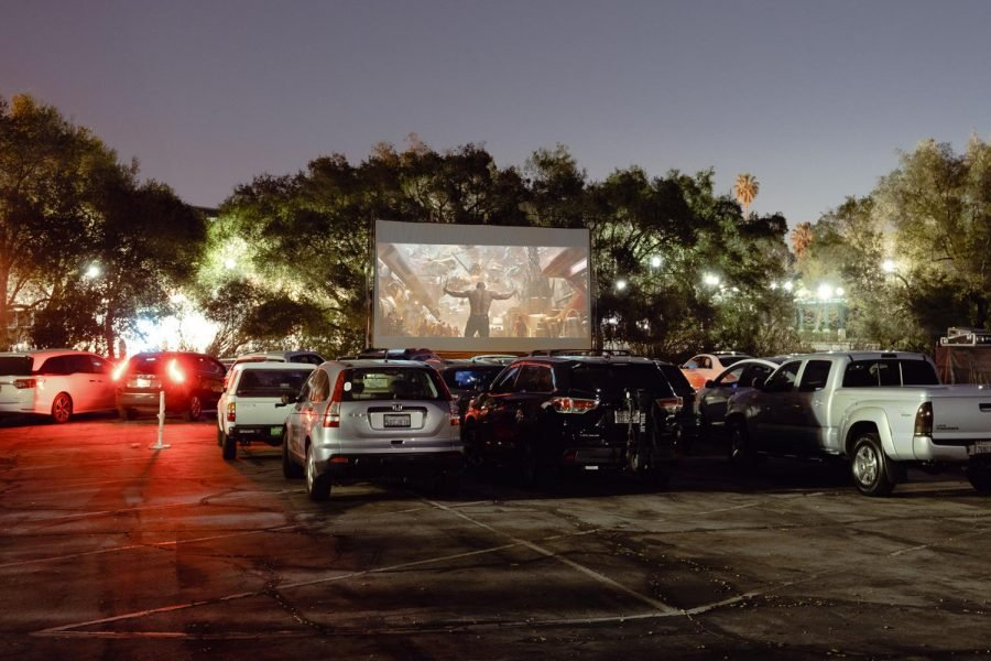 Cars are parked in front of a big projector screen that is showing a movie.