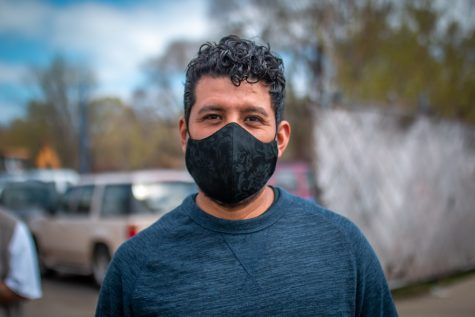 Man in a dark blue shirt with black curly hair and a black mask. A parking lot is blurred in the background.