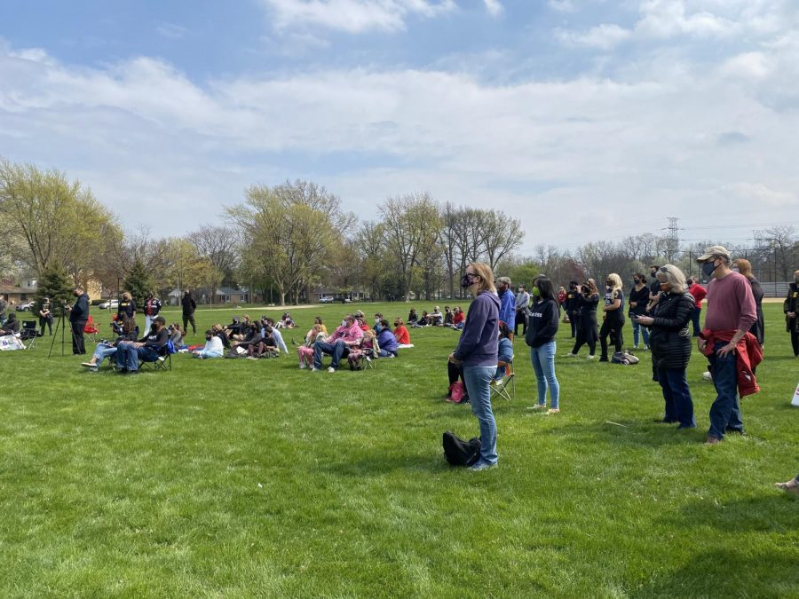A crowd gathers in a grassy park. People look toward a speaker not pictured.