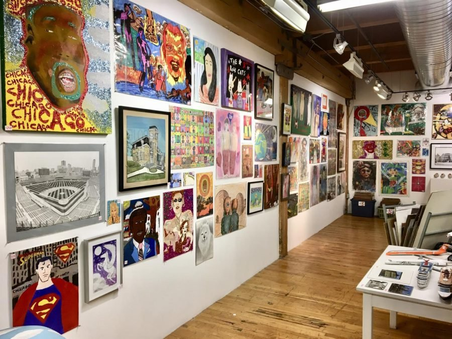 A wall of Project Onward's space displaying several paintings. Subjects include Superman, a baseball stadium, a black and white sketch of a dog, and a picture of a pegasus.
