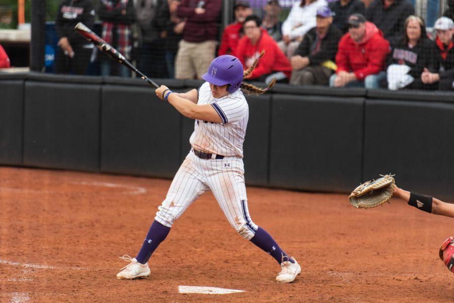 Nikki Cuchran swings metal bat in the air while wearing white striped softball uniform