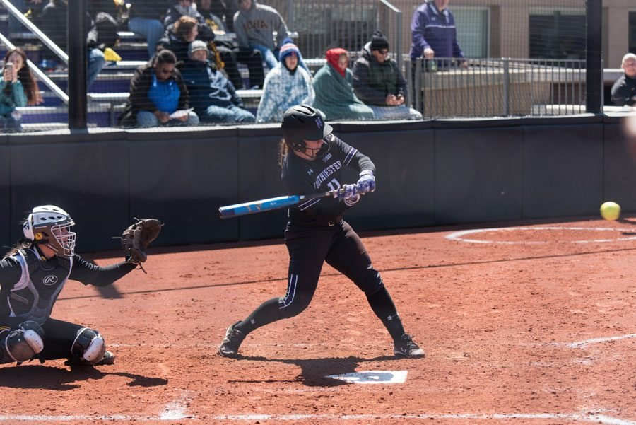 Northwestern player in black jersey prepares to swing bat on standing on brown diamond above a white home plate