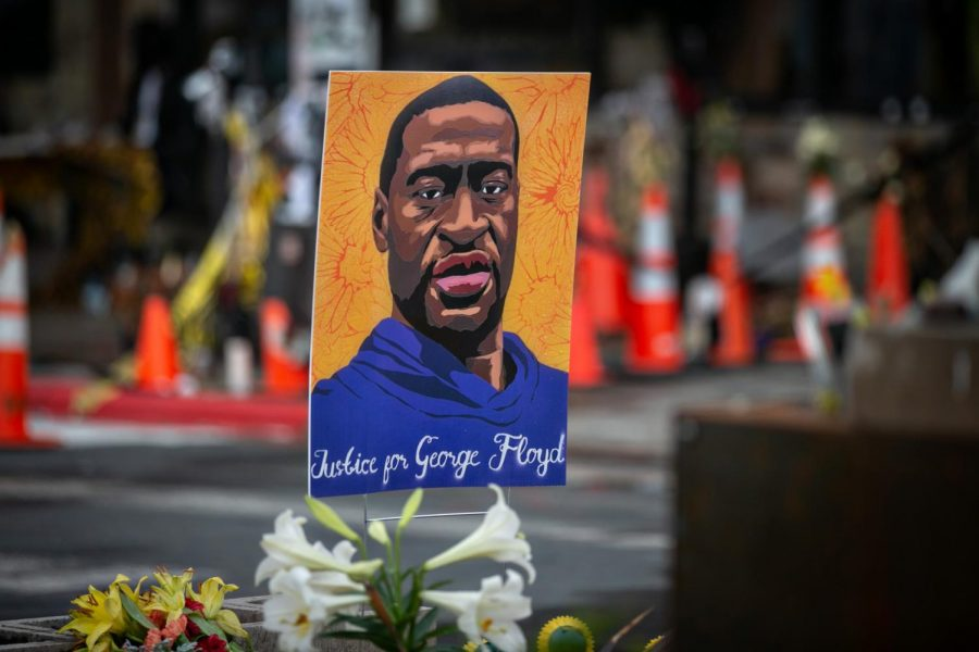 "A rectangular painting of George Floyd wearing a dark blue hoodie, with orange flowers in the background and the phrase ""Justice for George Floyd"" in white."