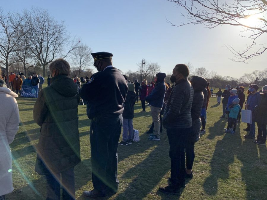 Over 150 Evanston residents stand on the lawn of a park. The grass is green and flat. There are barren trees in the background. The sky is blue and the sun is in the upper right corner.