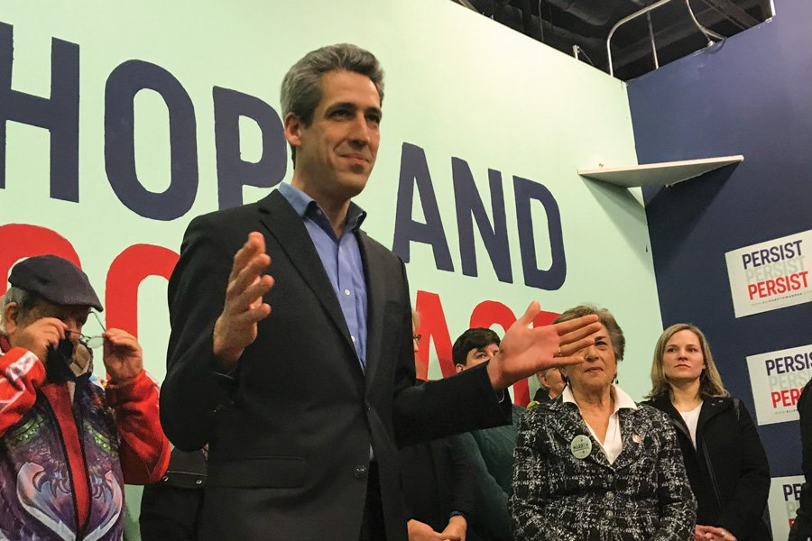 Daniel Biss stands in the center of the photo. He is wearing a light blue button-down shirt with a charcoal suit-jacket buttoned in the middle. Biss is making a hand-gesture as he speaks. There is a green wall and four more people in the background.