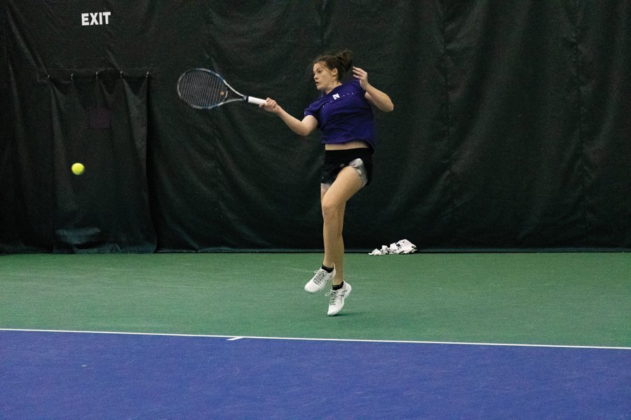 A tennis player goes for the ball on the tennis court.